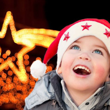 Young child looking up at a light wearing a Santa hat