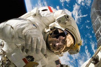 An astronaut floating in space with earth behind him