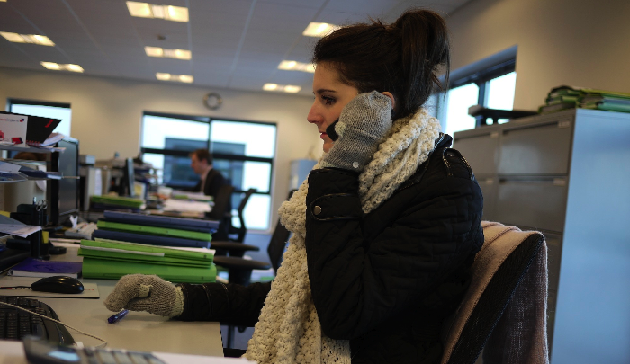 A woman sitting in the office with gloves on